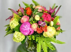 A lush bouquet of pinks, reds and yellows, on display in a deep green ceramic vase